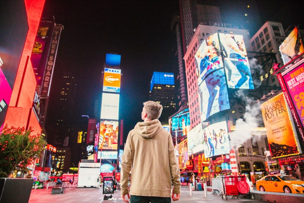 Young man in Times Square looking at neon signs